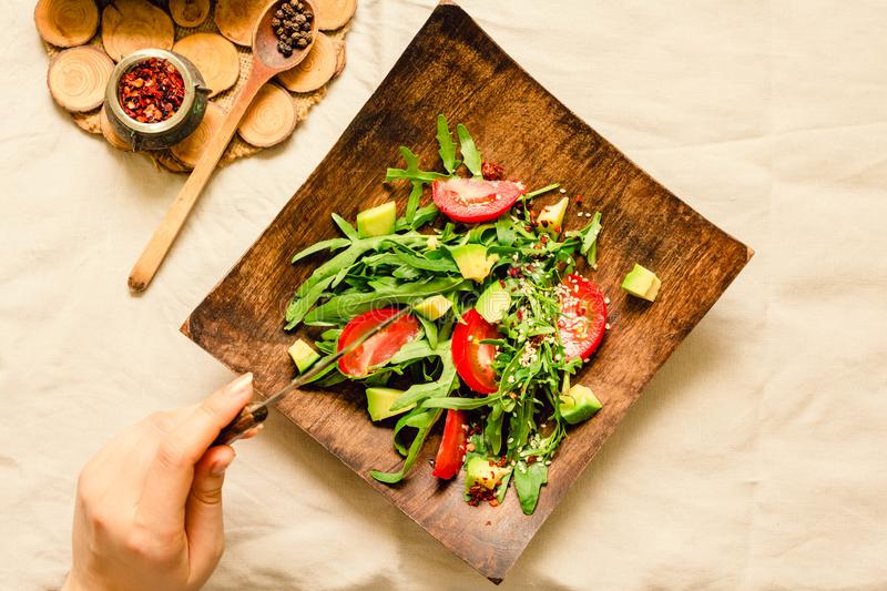 Fresh light green salad with avocado and tomatoes in a wooden plate. Top view. The process of eating. royalty free stock image