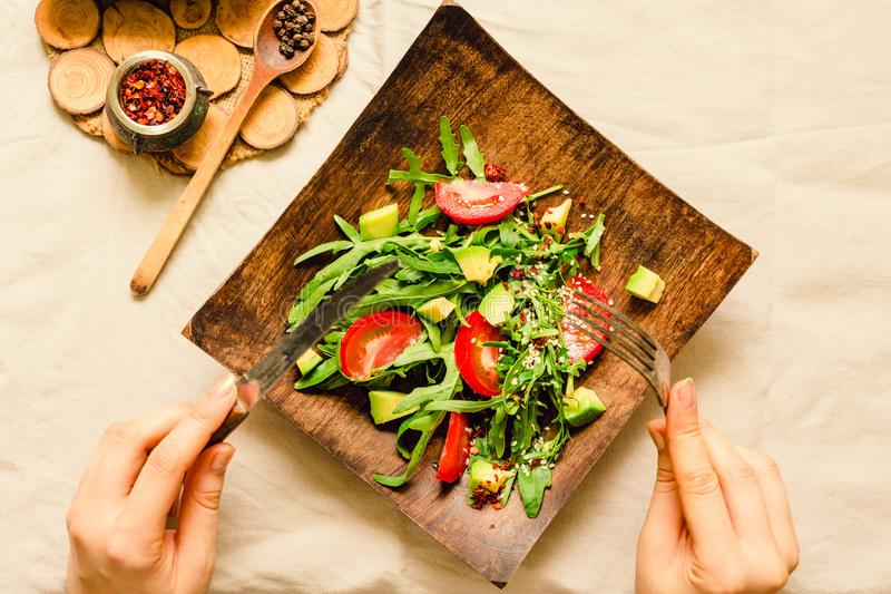 Fresh light green salad with avocado and tomatoes in a wooden plate. Top view. The process of eating. stock photos