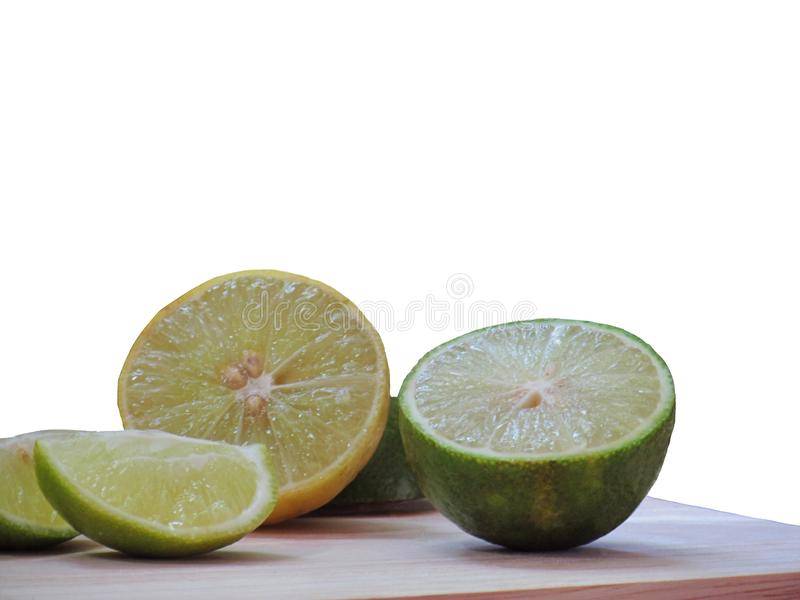 Fresh lime, cut in half and sliced on a wooden cutting board isolated on white background. royalty free stock photography