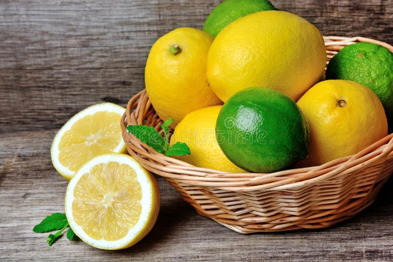 Fresh lime and lemon in a basket on a rustic wood table stock image