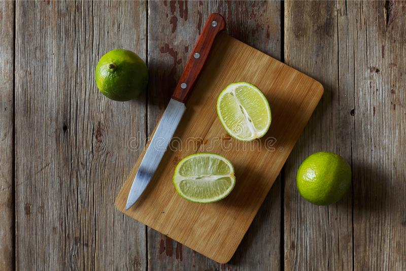 Fresh lime whole and cut into pieces on a wooden table. Rural style closeup. royalty free stock photo