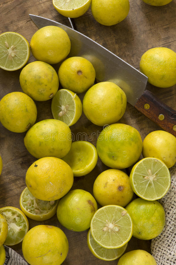 Fresh limes on wooden background. Sliced with knife for juice royalty free stock images