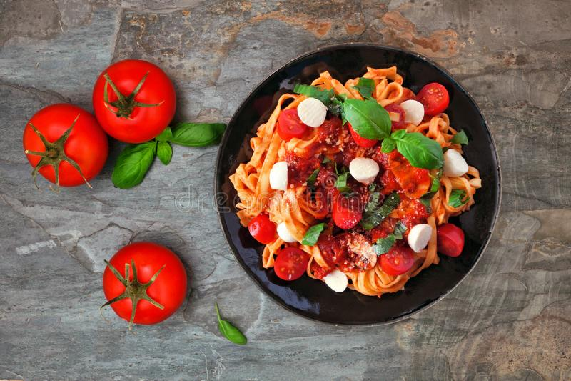 Linguine pasta with tomatoes, mozzarella and basil, top view scene over dark slate stock photos