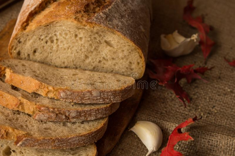 A fresh loaf of bread. Sliced ​​fresh bread in composition with aun leaves and garlic royalty free stock images