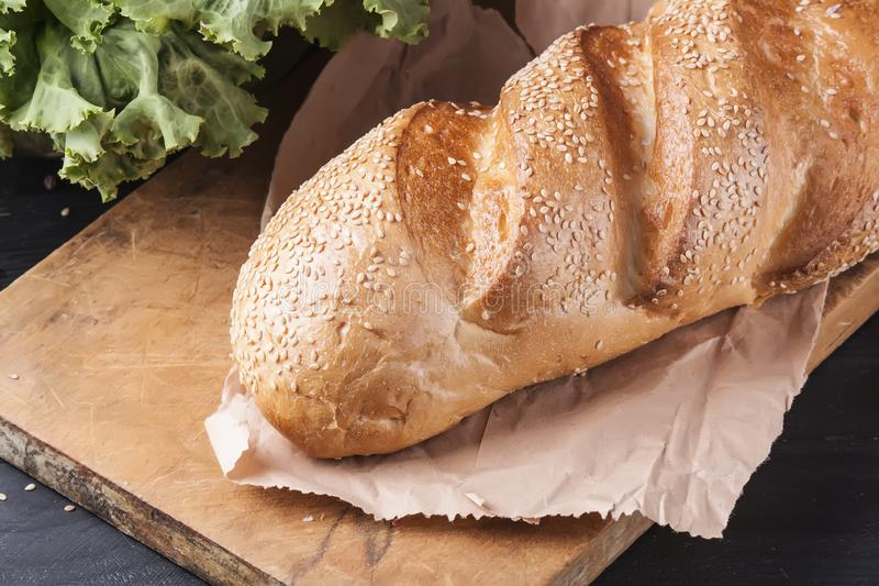 Fresh loaf sprinkled with sesame seeds on a wooden table. Delicious baking stock photos