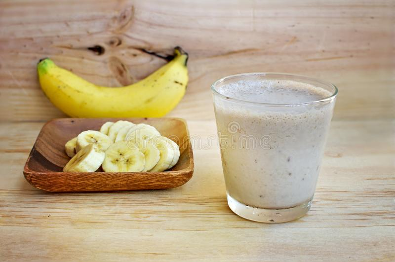 Fresh home made Banana smoothie on wooden background stock photos
