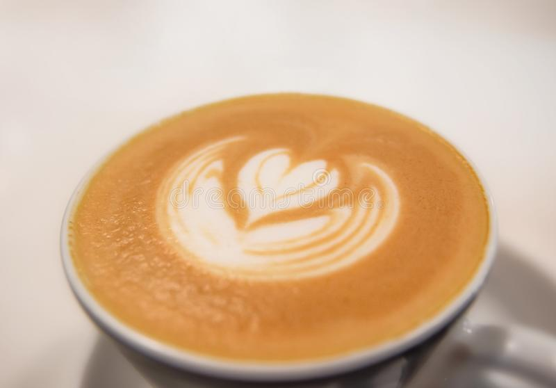 Fresh made cappuccino made by barista on white table in cafeteria. Close royalty free stock photo