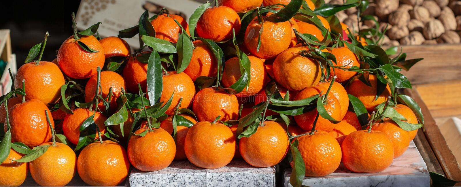 Fresh Mandarins and Clementines Orange Stack, with Leaves, on sale, in the sunlight. Vitamin and healthy Food. stock images
