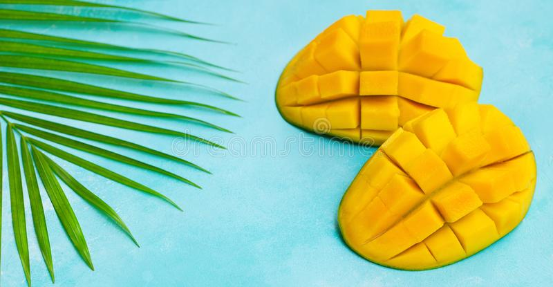 Fresh mango organic product on a palm leaf. Blue background. Copy space. Top view. stock image