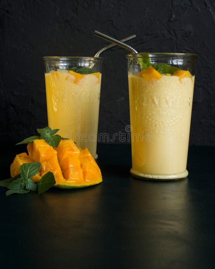 Mango smoothie / mango lassi in vintage glass cups on a dark surface with metal straws. with mint leaves and a slice of ripe and j. Fresh mango smoothie / mango royalty free stock photography
