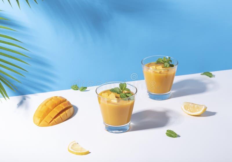 Fresh mango smoothie and ripe mango slice on color background. summer drink.  stock images