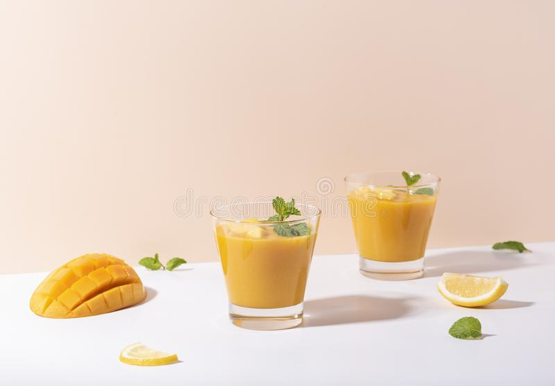 Fresh mango smoothie and ripe mango slice on color background. summer drink.  royalty free stock images