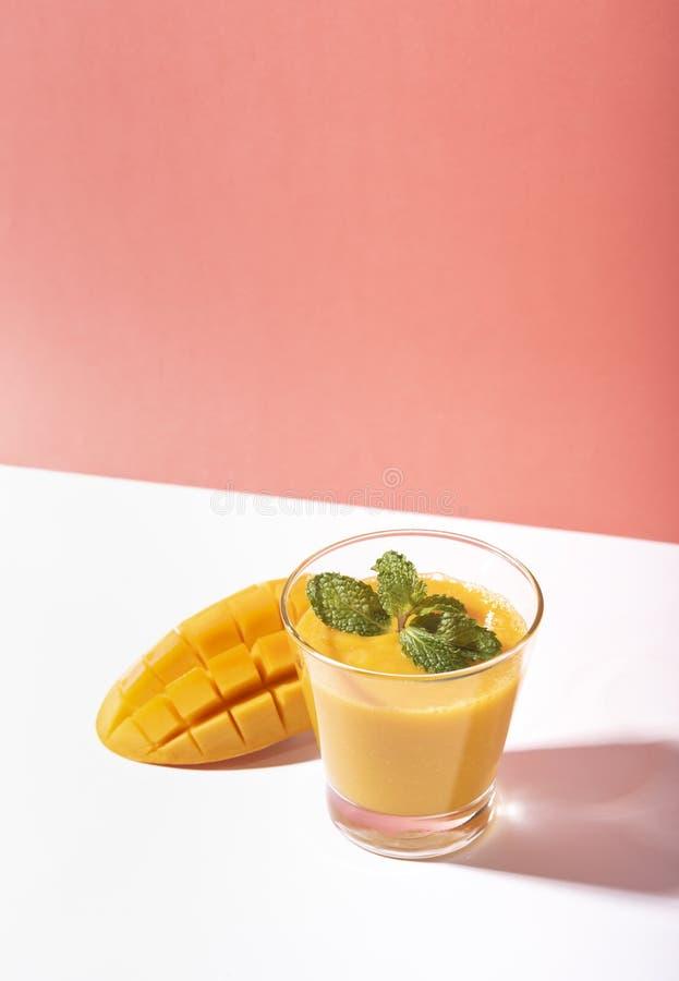 Fresh mango smoothie and ripe mango slice on color background. summer drink.  royalty free stock image