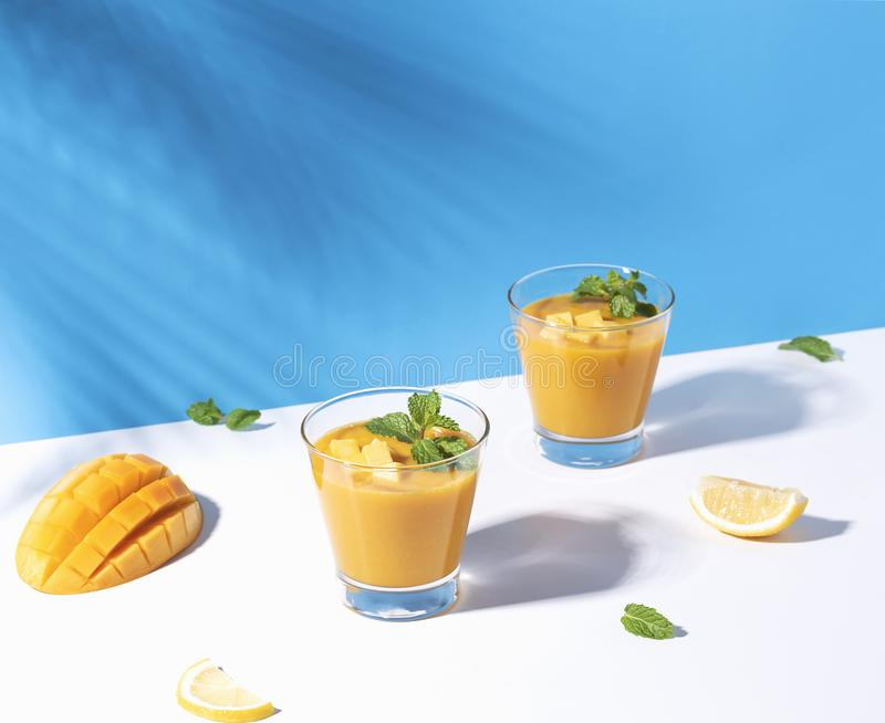 Fresh mango smoothie and ripe mango slice on color background. summer drink.  royalty free stock photo