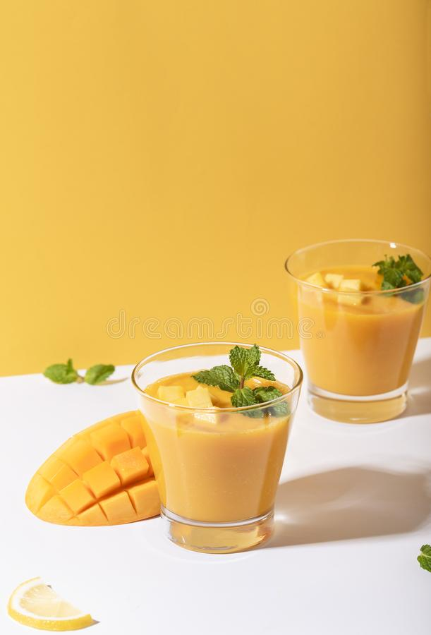 Fresh mango smoothie and ripe mango slice on color background. summer drink.  royalty free stock photography