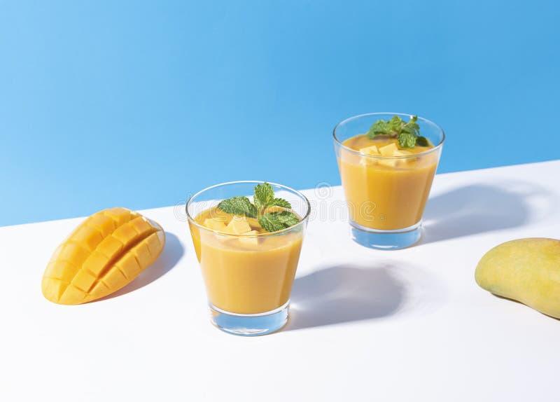 Fresh mango smoothie and ripe mango slice on color background. summer drink.  stock photography