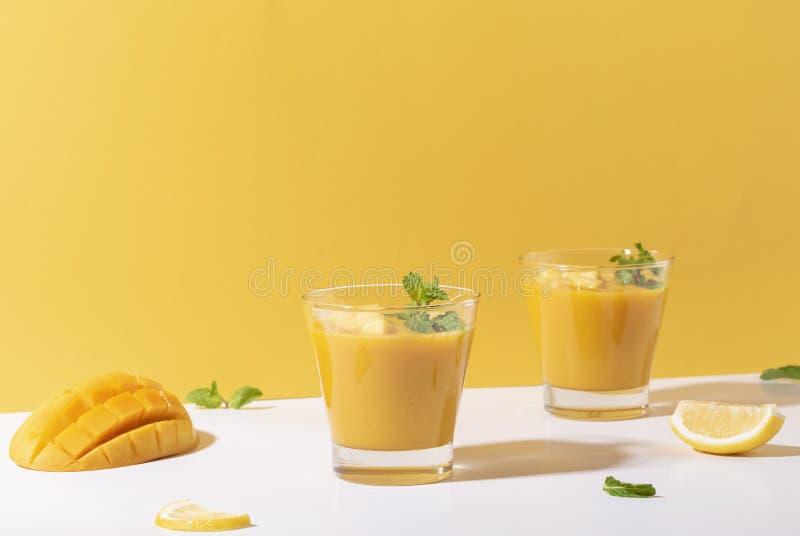 Fresh mango smoothie and ripe mango slice on color background. summer drink.  stock image