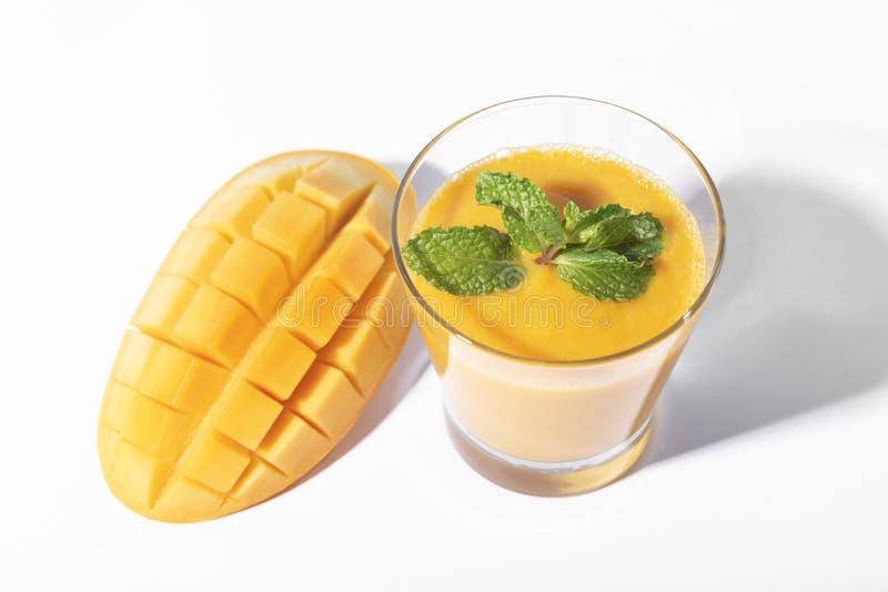 Fresh mango smoothie and ripe mango slice on white background. summer drink.  royalty free stock images