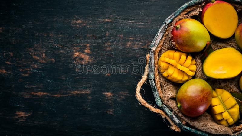 Fresh mango in a wooden box. On a wooden background. Tropical Fruits. stock photos