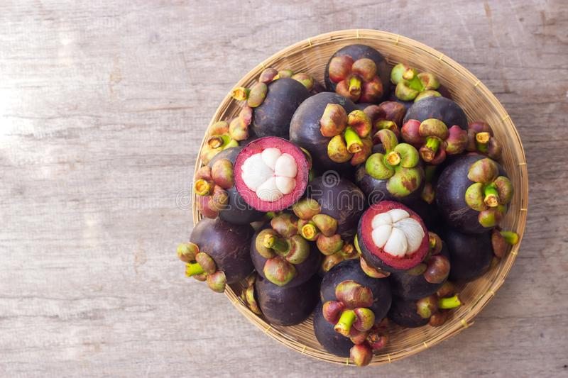 Fresh mangosteen in bamboo basket. Top view with copy space on wooden table. Healthy and sweet fruit. High vitamins royalty free stock image