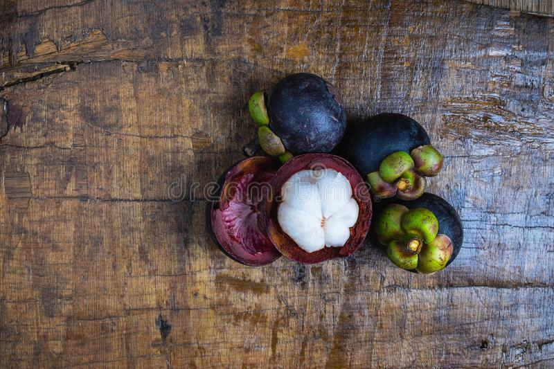 Fresh mangosteen fruit on a wooden table. royalty free stock image