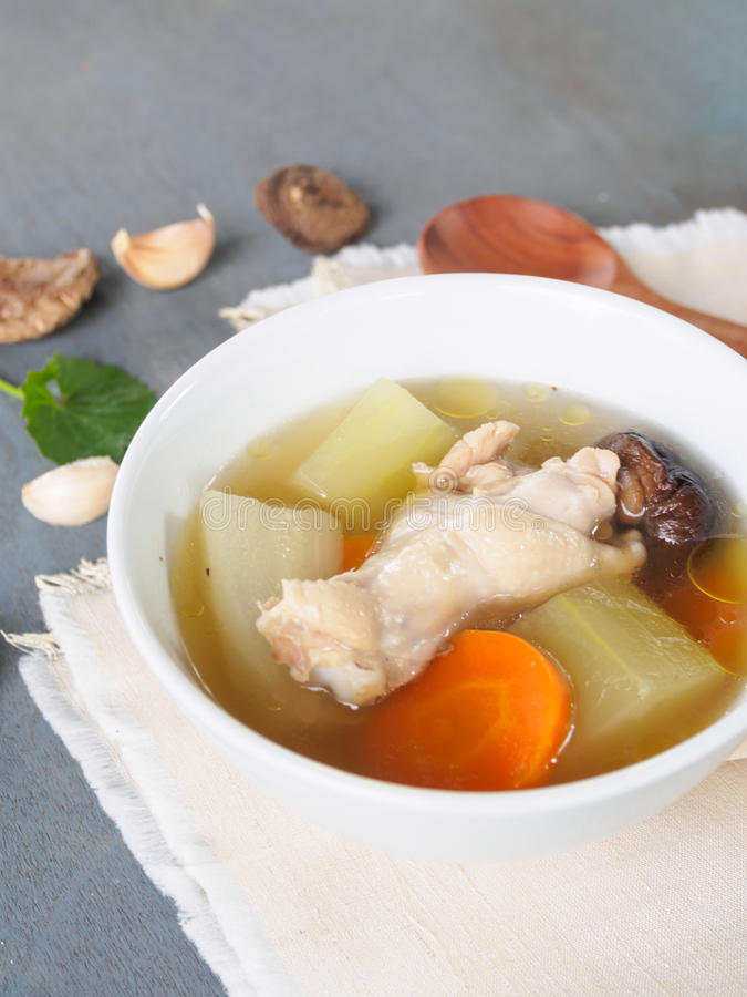Fresh marrow squash soup in white bowl on wooden table stock image