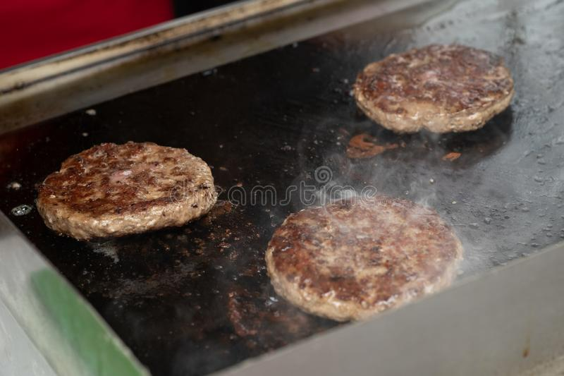 Fresh meat cutlets in a frying pan grill stock photos