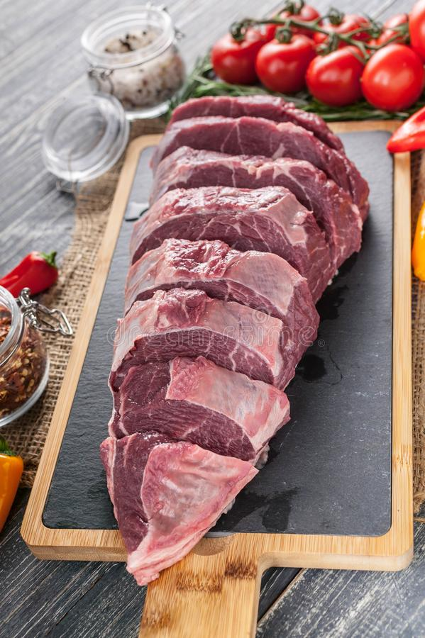 Raw Black Angus meat and vegetables. Fresh meat on a cutting board. Vertical shot. Fresh meat on a cutting board. Vertical shot. Raw Black Angus meat and royalty free stock image