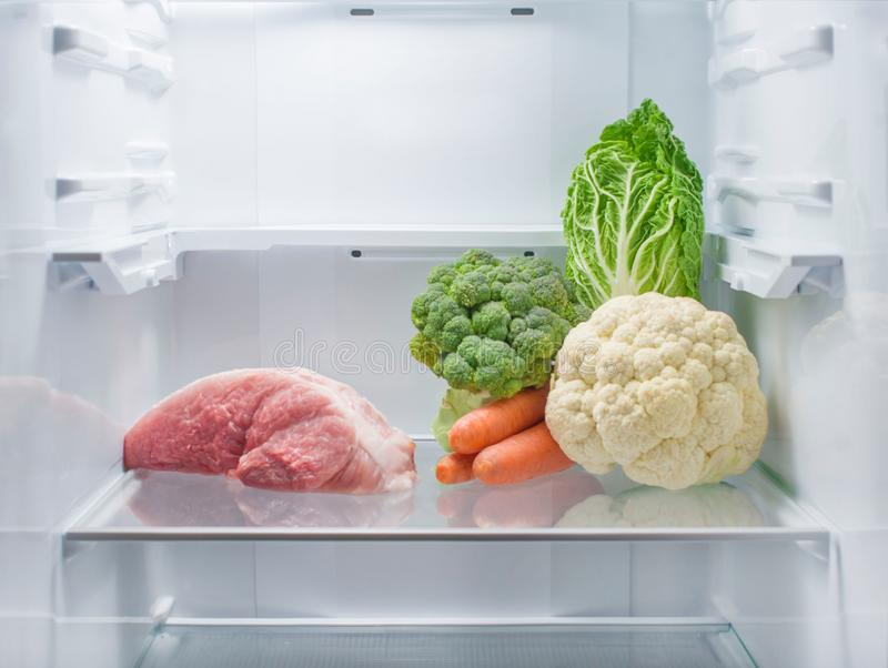 Fresh meat and fresh vegetables opposite each other in an empty refrigerator. The choice between vegetarianism and meat-eating royalty free stock photo