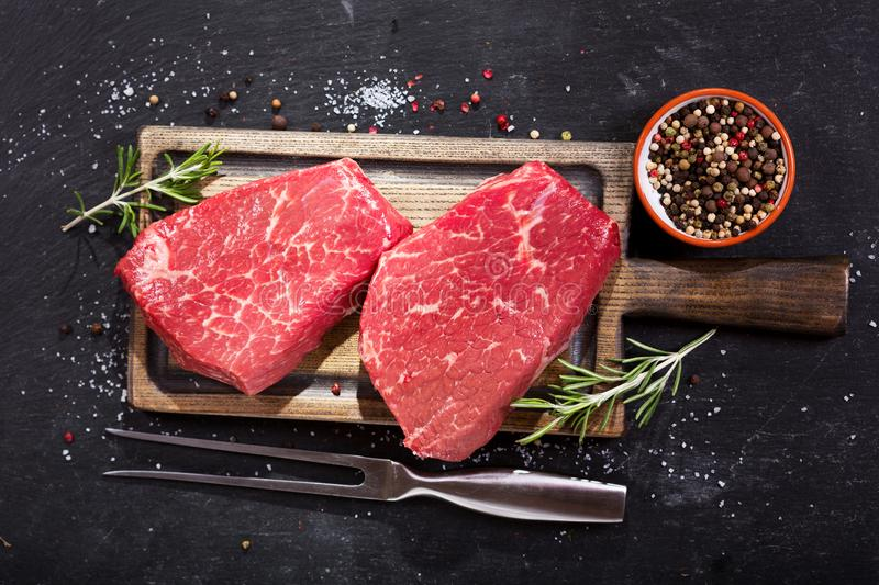 Fresh meat with ingredients for cooking, top view. Fresh meat with ingredients for cooking on dark background, top view stock images