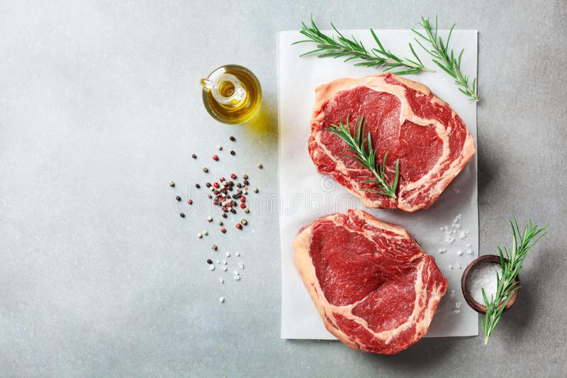 Fresh meat on kitchen table top view. Raw beef steak and spices for cooking royalty free stock image