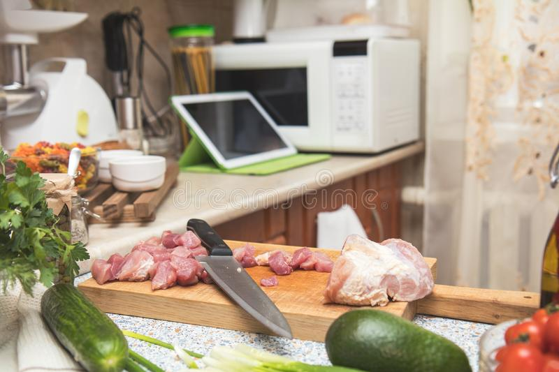 Fresh meat and knife on cutting board in the kitchen table.Small cozy kitchen with household appliances. Cozy home concept royalty free stock photos