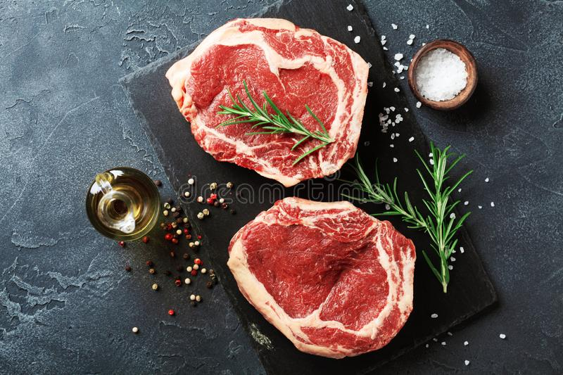 Fresh meat on slate black board top view. Raw beef steak and spices for cooking royalty free stock photography