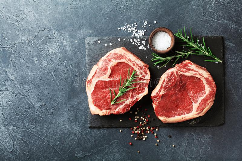 Fresh meat on slate black board top view. Raw beef steak and spices for cooking royalty free stock photo