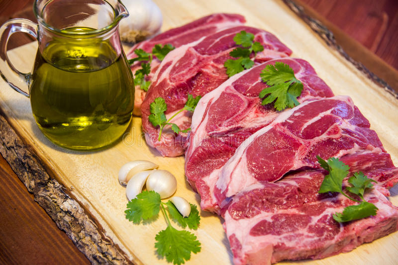 Fresh Meat. Fresh meat, Raw Meat. 4 steaks, with olive oil and garlic decoration royalty free stock photo