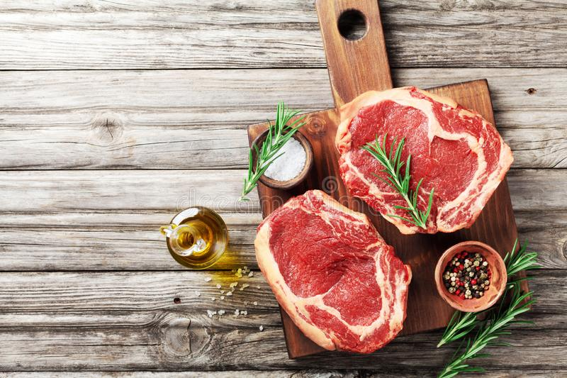 Fresh meat on wooden cutting board top view. Raw beef steak and spices for cooking stock image