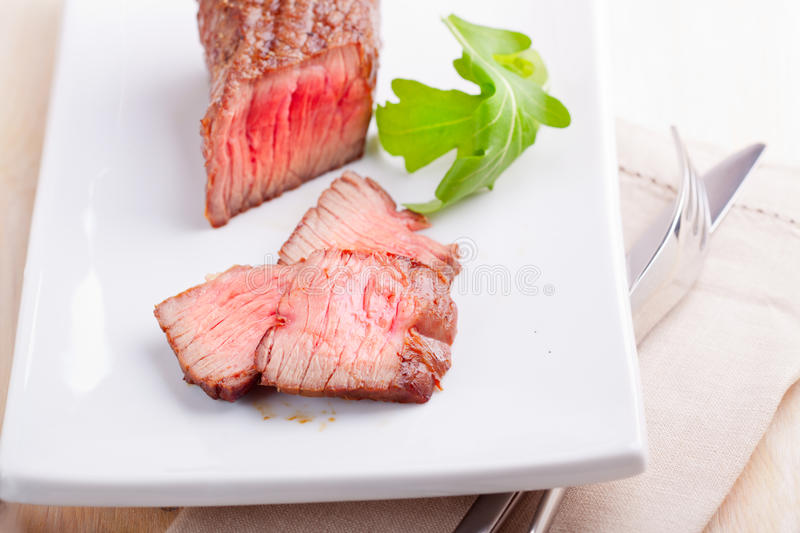 Fresh medium grilled steak. Close-up of delicious filet mignon with herb stock photo