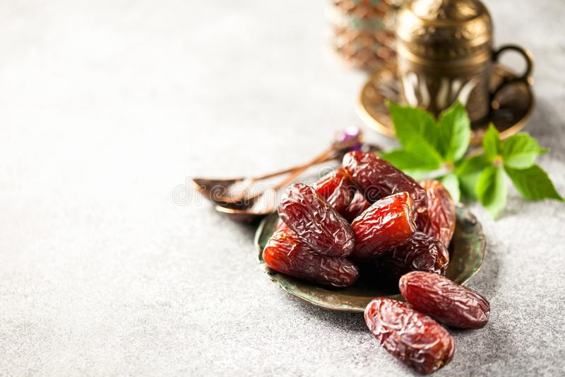 Fresh Medjool Dates. In a bowl with coffee. Ramadan kareem. Grey background stock photo