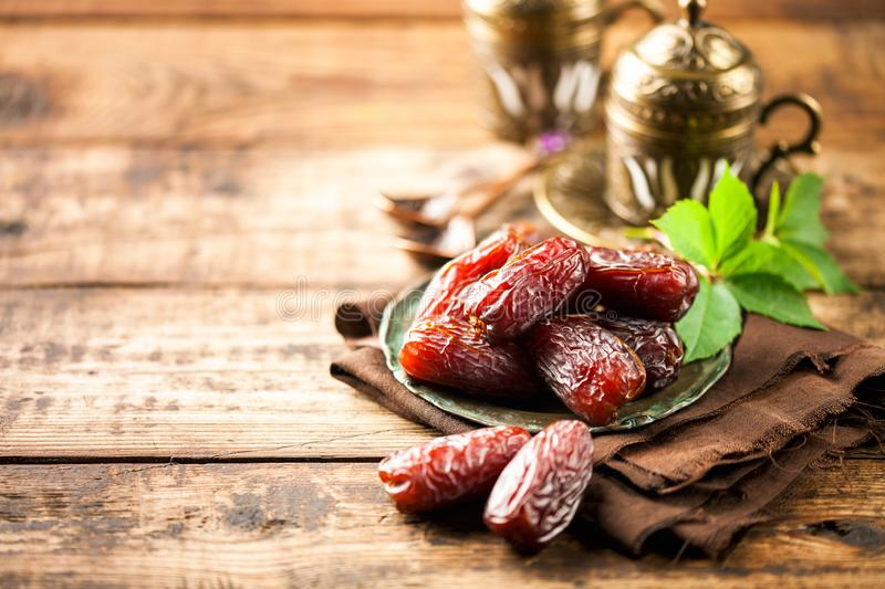 Fresh Medjool Dates. In a bowl with coffee on wooden background.. Ramadan kareem royalty free stock photography