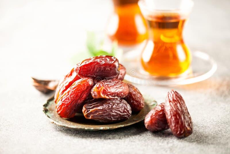 Fresh Medjool Dates. In a bowl with tea. Ramadan kareem. Grey background royalty free stock photo