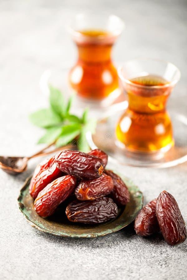 Fresh Medjool Dates. In a bowl with tea. Ramadan kareem. Grey background royalty free stock images