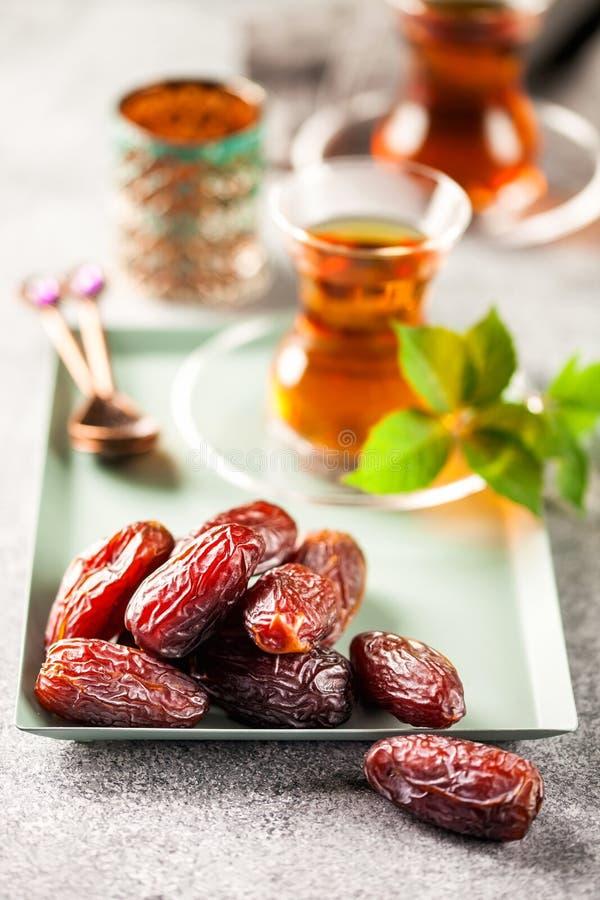 Fresh Medjool Dates. In a bowl with tea. Ramadan kareem. Grey background stock photos