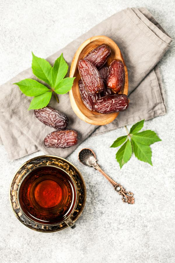 Fresh Medjool Dates. In a bowl with tea. Ramadan kareem. Grey wooden background. Top view royalty free stock images