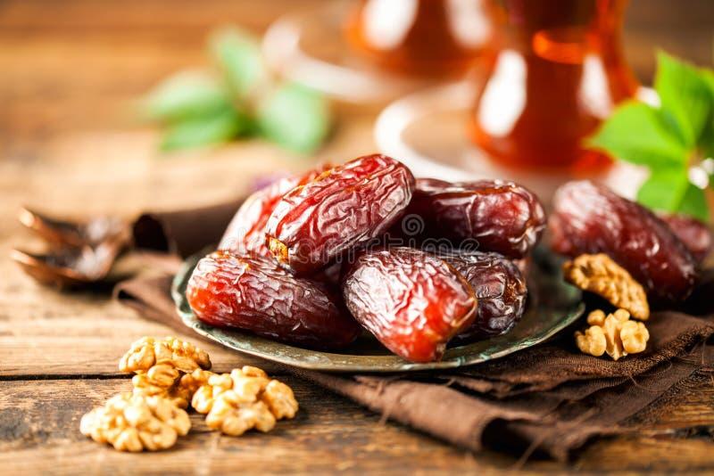 Fresh Medjool Dates. In a bowl with tea on wooden background.. Ramadan kareem stock photography