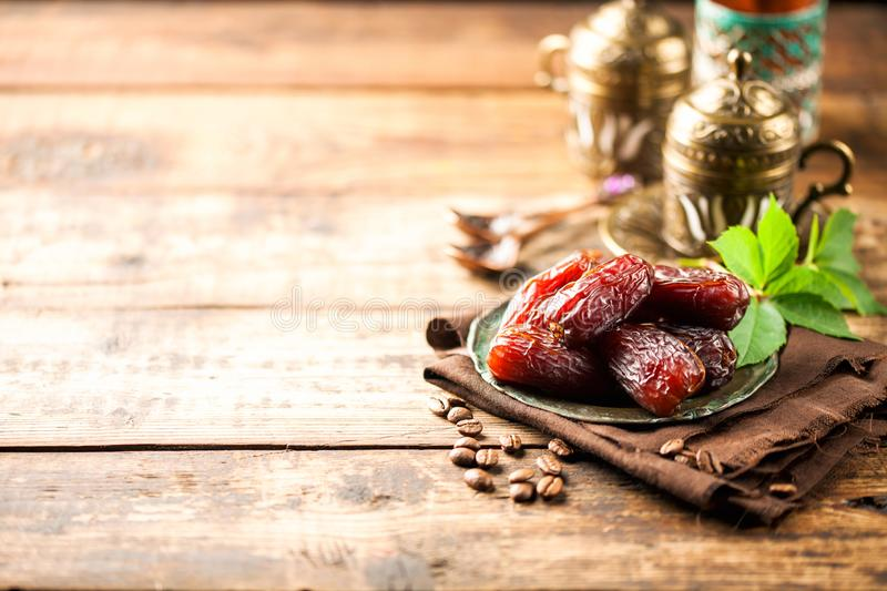 Fresh Medjool Dates. In a bowl with coffee on wooden background.. Ramadan kareem royalty free stock image