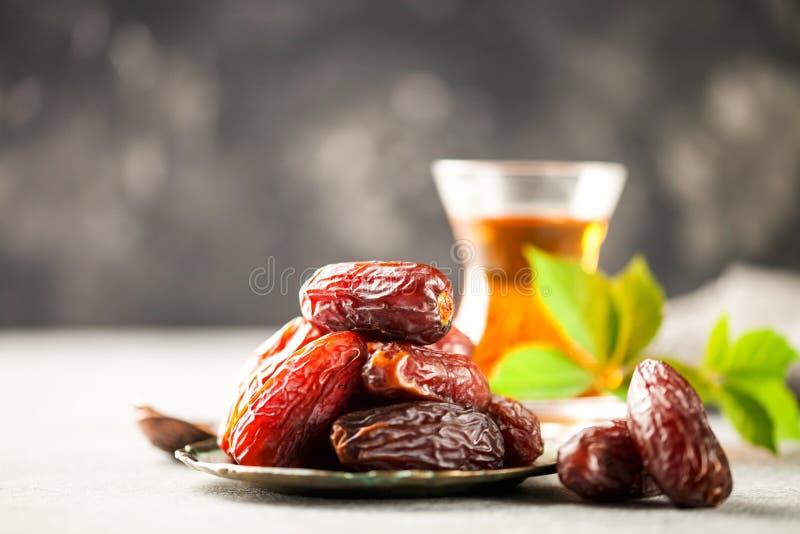 Fresh Medjool Dates. In a bowl with tea. Ramadan kareem. Grey background stock image