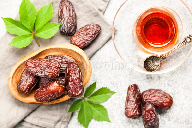Fresh Medjool Dates. In a bowl with tea. Ramadan kareem. Grey wooden background. Top view royalty free stock image