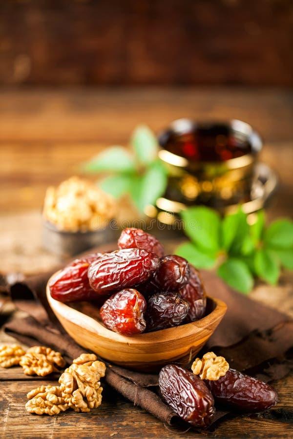 Fresh Medjool Dates. In a bowl with tea on wooden background.. Ramadan kareem stock image