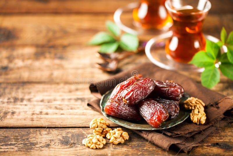 Fresh Medjool Dates. In a bowl with tea on wooden background.. Ramadan kareem stock photo
