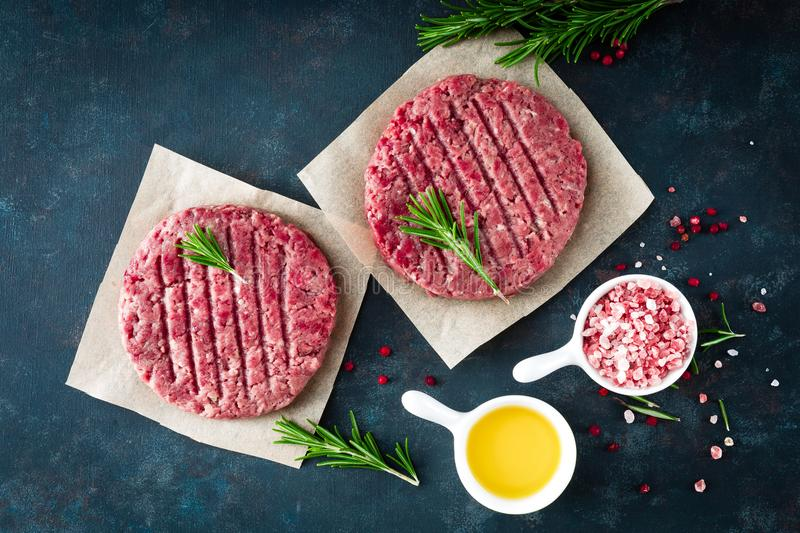 Fresh minced beef meat burgers with spices on dark background. Raw ground beef meat stock images